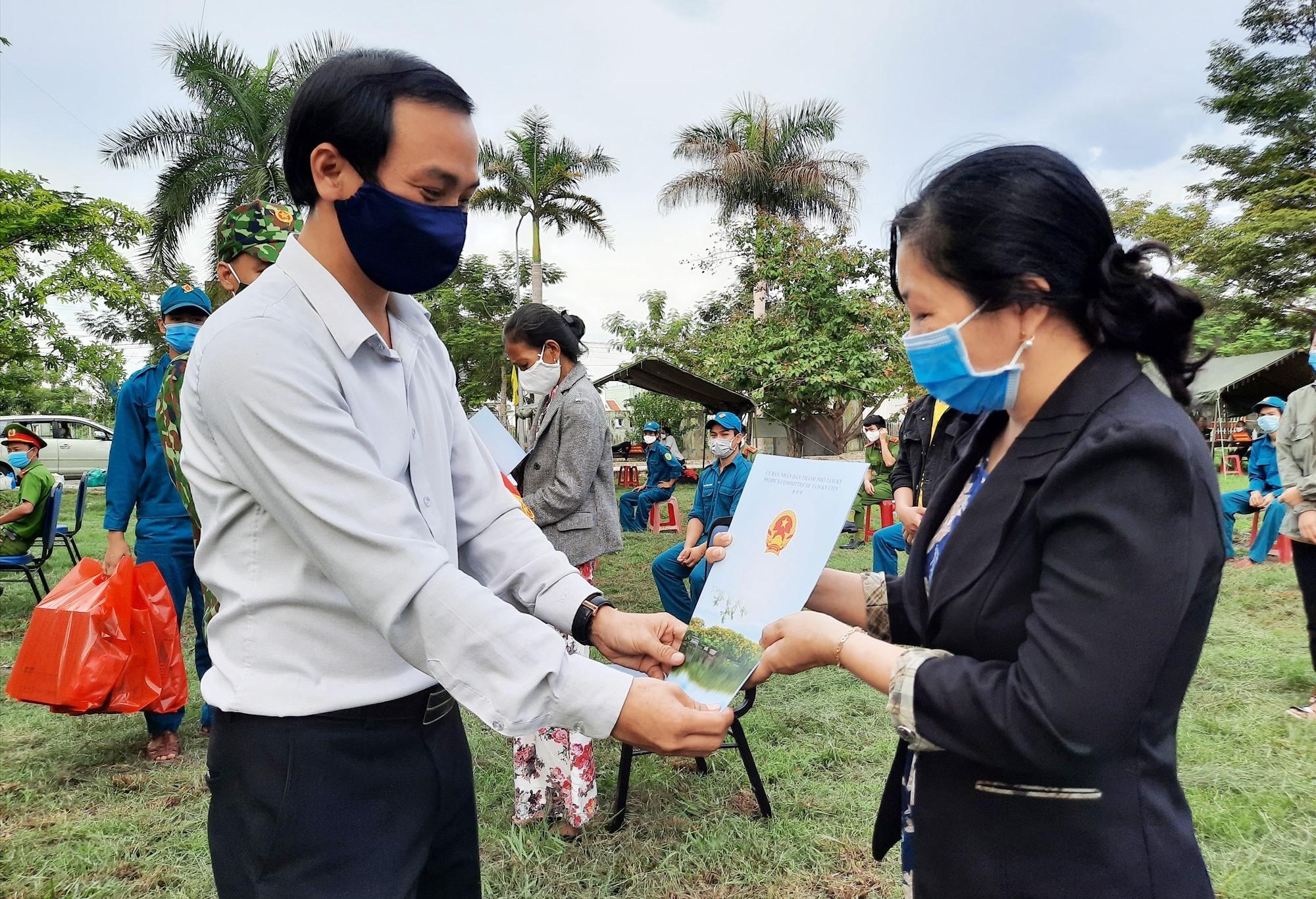 Phó Chủ tịch UBND TP.Tam Kỳ Nguyễn Hồng Lai trao giấy xác nhận hoàn thành cách ly y tế tập trung cho 19 công dân. Ảnh: Đ. ĐẠO