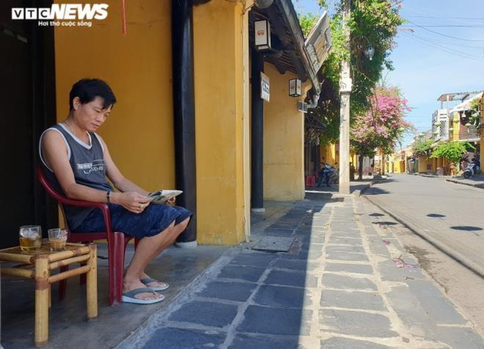 A man sitting in front of a quiet street. Photo: vtcnews