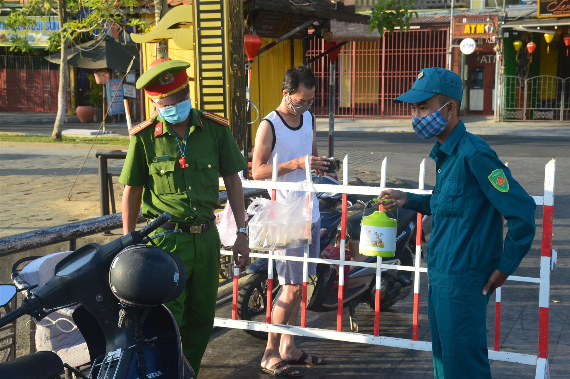 Người dân trong khu vực phong tỏa được lực lượng tại chốt kiểm soát hỗ trợ mua thức ăn. Ảnh: Q.T