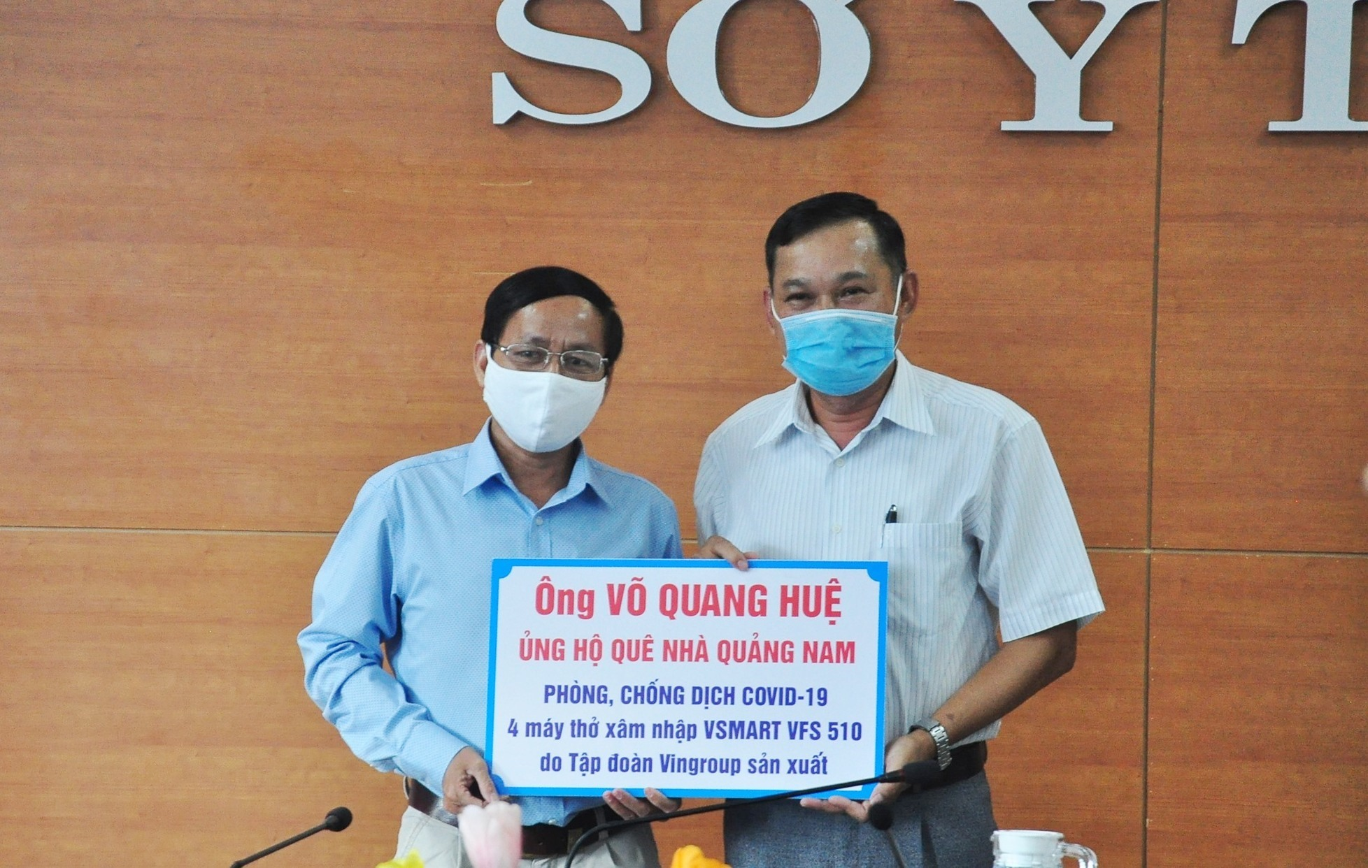 A representative of Mr. Hue's family (R) gives the symbol of 4 ventilators worth VND740 million to the Quang Nam provincial Department of Health.