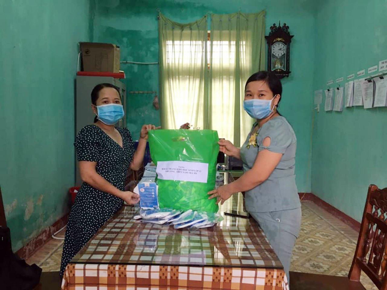 Cô Lê Thị Hồng Thanh (bên phải) trao khẩu trang các mạnh thường quân tặng học sinh Trường THPT Nam Trà My trước kỳ thi THPT quốc gia. Ảnh: M.HẠNH