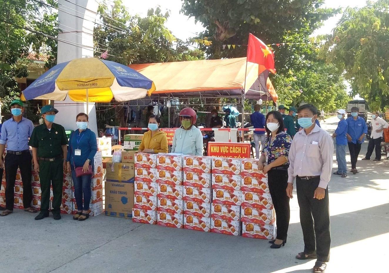 Tặng nhu yếu phẩm cần thiết cho người dân trong khu vực đang bị phong tỏa tạm thời tại xã Điện Trung. Ảnh: NGỌC TUẤN