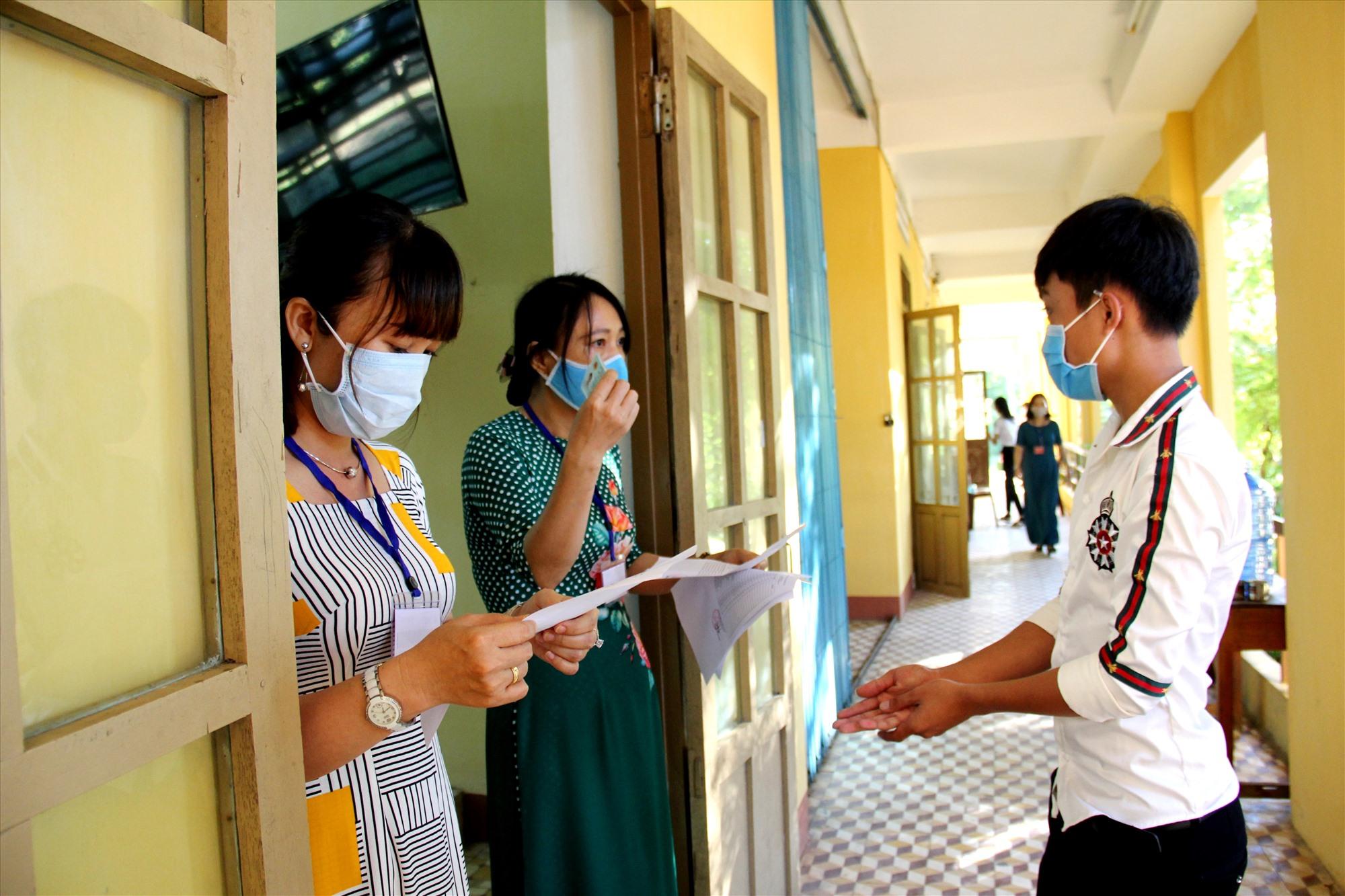 Ảnh 3 các cán bộ coi thi thực hiện nội quy kiểm tra thí sinh trước khi vào phòng thi