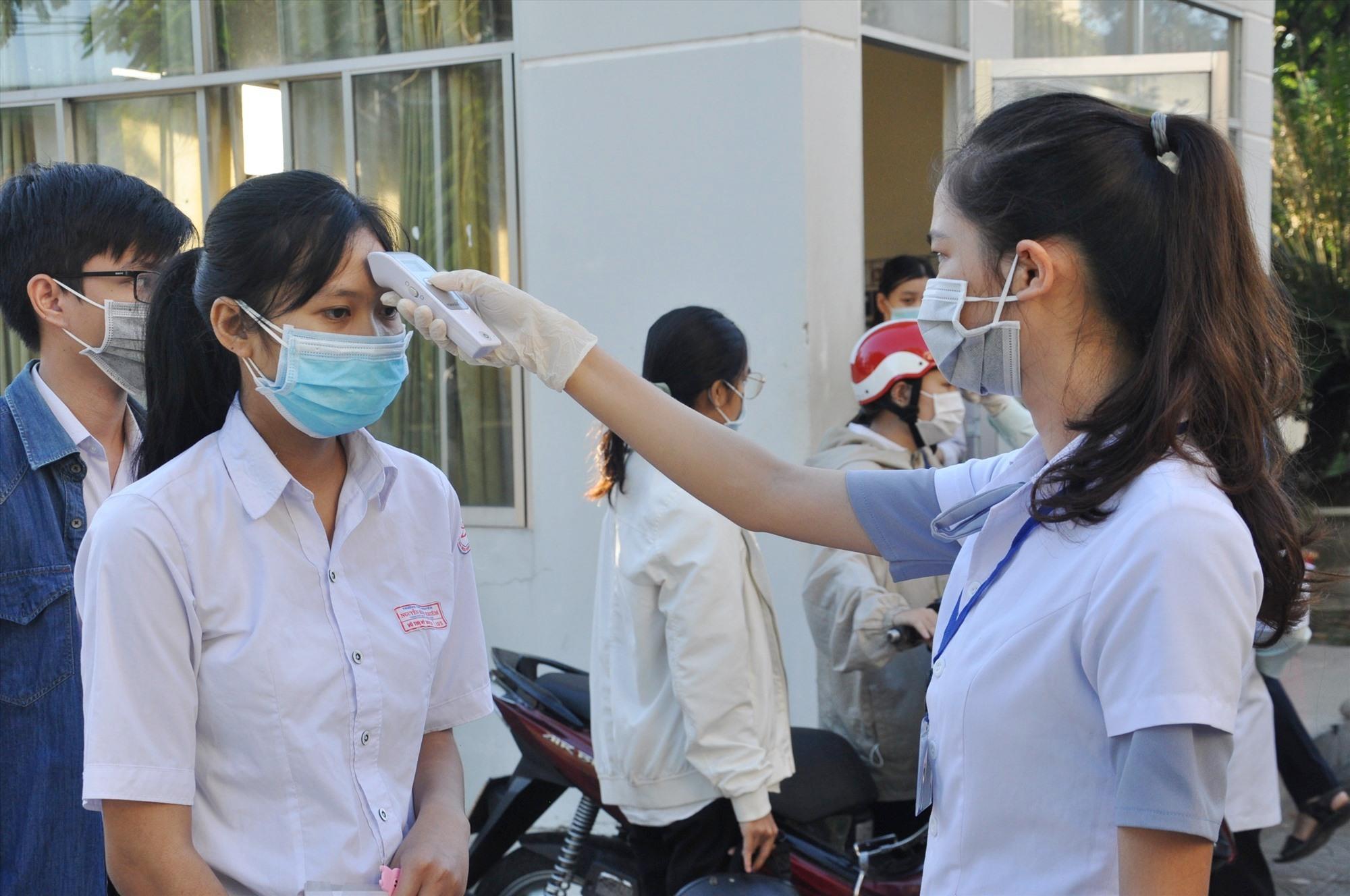 Đo thân nhiệt các TS tại Trường THPT chuyên Nguyễn Bỉnh Khiêm. Ảnh: X.P