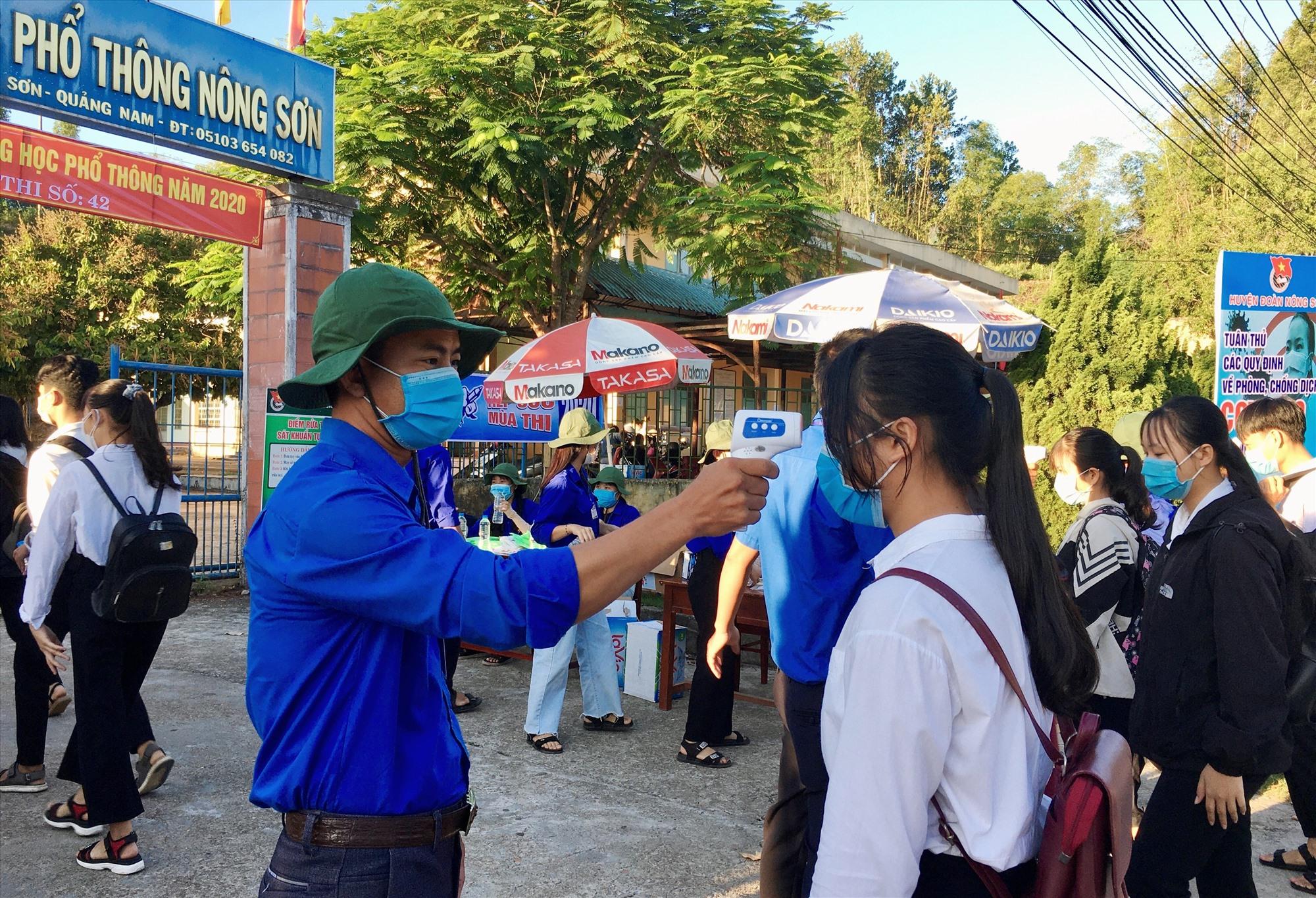 Các tình nguyện viên tiếp sức mùa thi đo thân nhiệt cho thí sinh trước khi bước vào điểm thi.