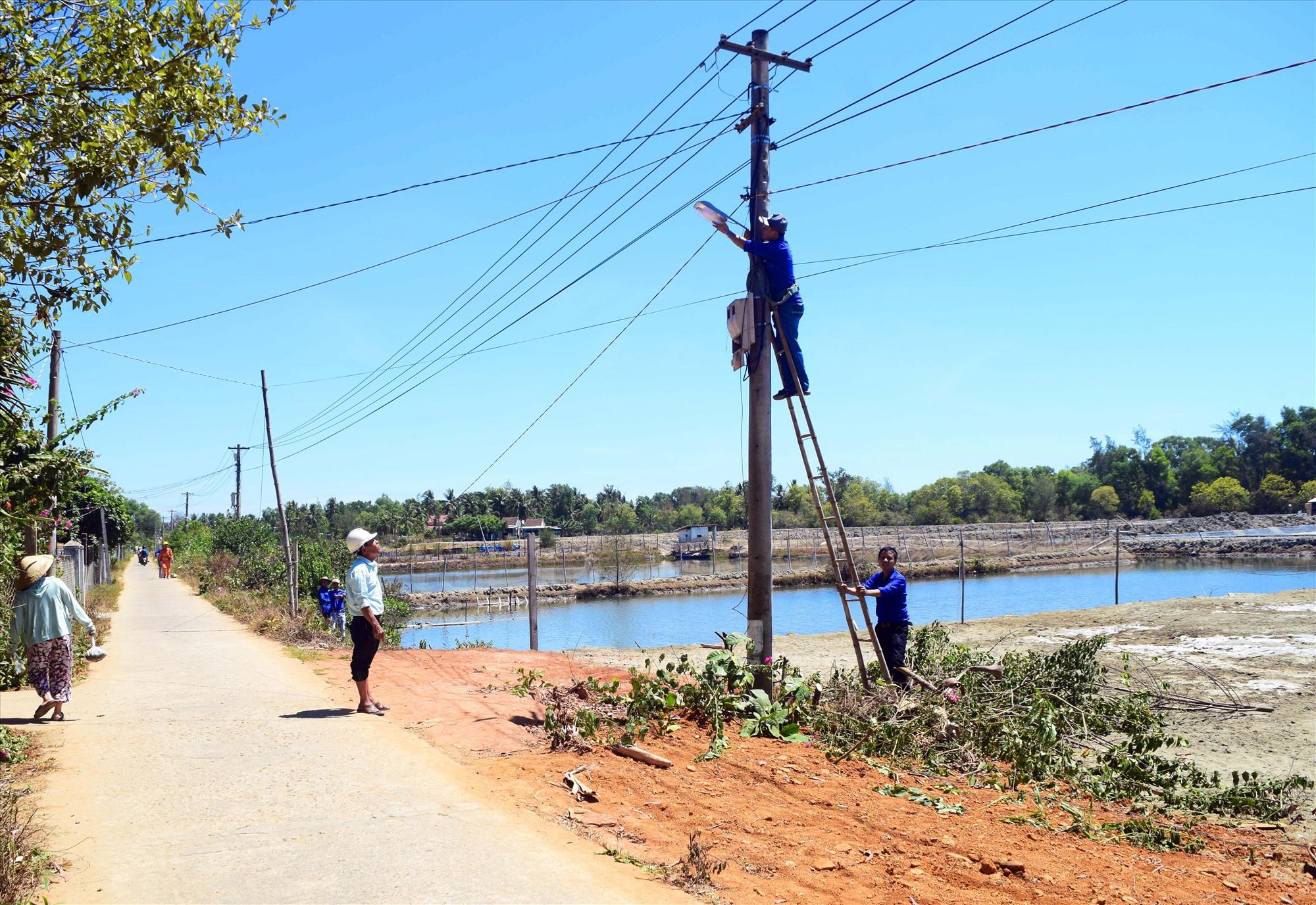 Đoàn viên thanh niên thực hiện công trình thắp sáng đường quê tại thôn Đông Thạnh (xã Tam Hòa). Ảnh: THÁI CƯỜNG