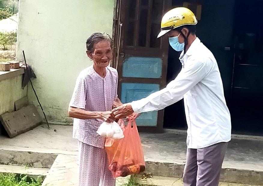 Thầy Nguyễn Tấn Sinh trao quà cho những gia đình neo đơn, có hoàn cảnh khó khăn bị ảnh hưởng bởi dịch Covid-19. Ảnh: T.P