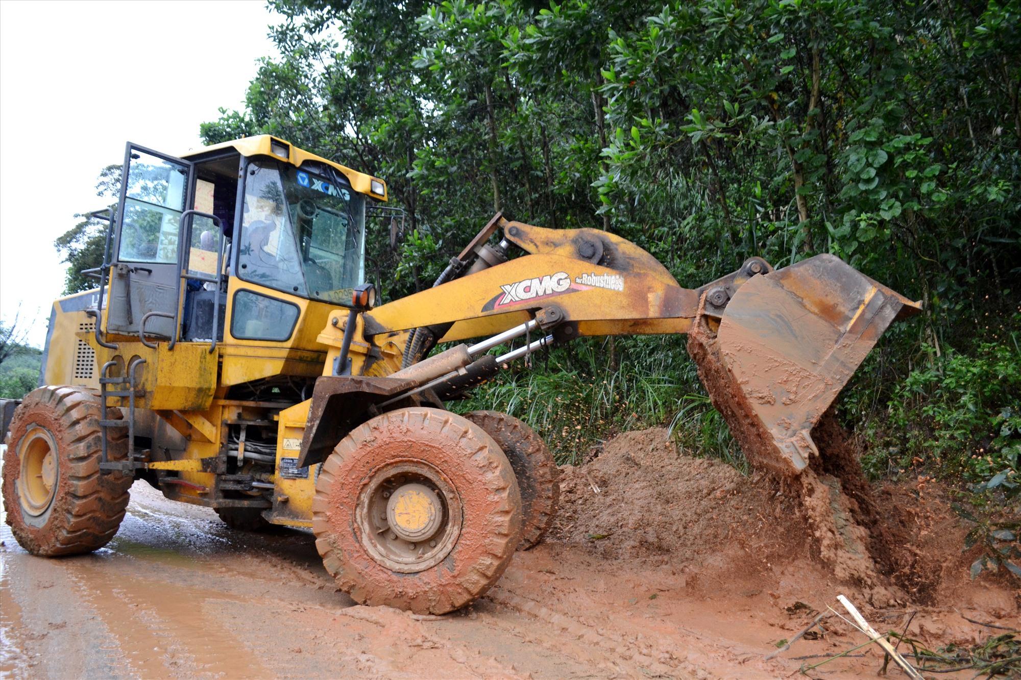 Công nhân Công ty CP Công trình GTVT Quảng Nam xúc dọn đất, đá sạt lở do mưa lũ gây tắc lưu thông trên quốc lộ 14E. Ảnh: C.T