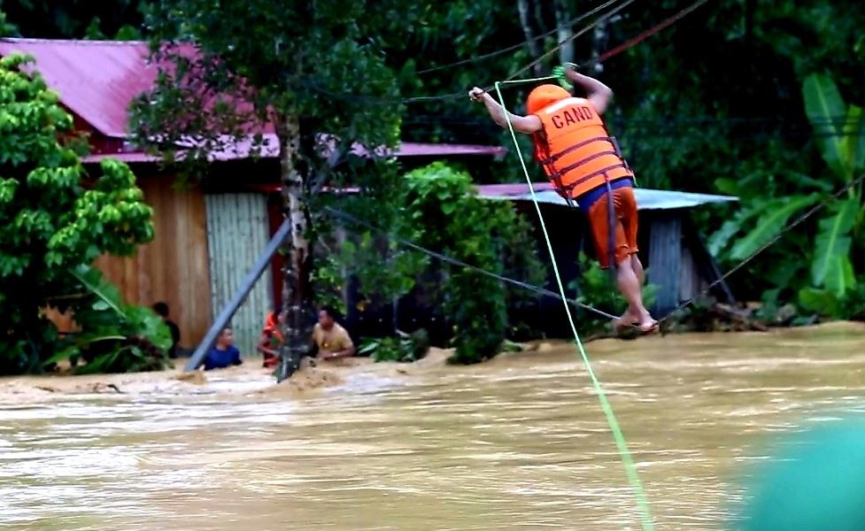 Để qua được dòng lũ, đội cứu hộ huyện Tây Giang đã phải đu theo đường dây đầy mạo hiểm. Ảnh: H.T