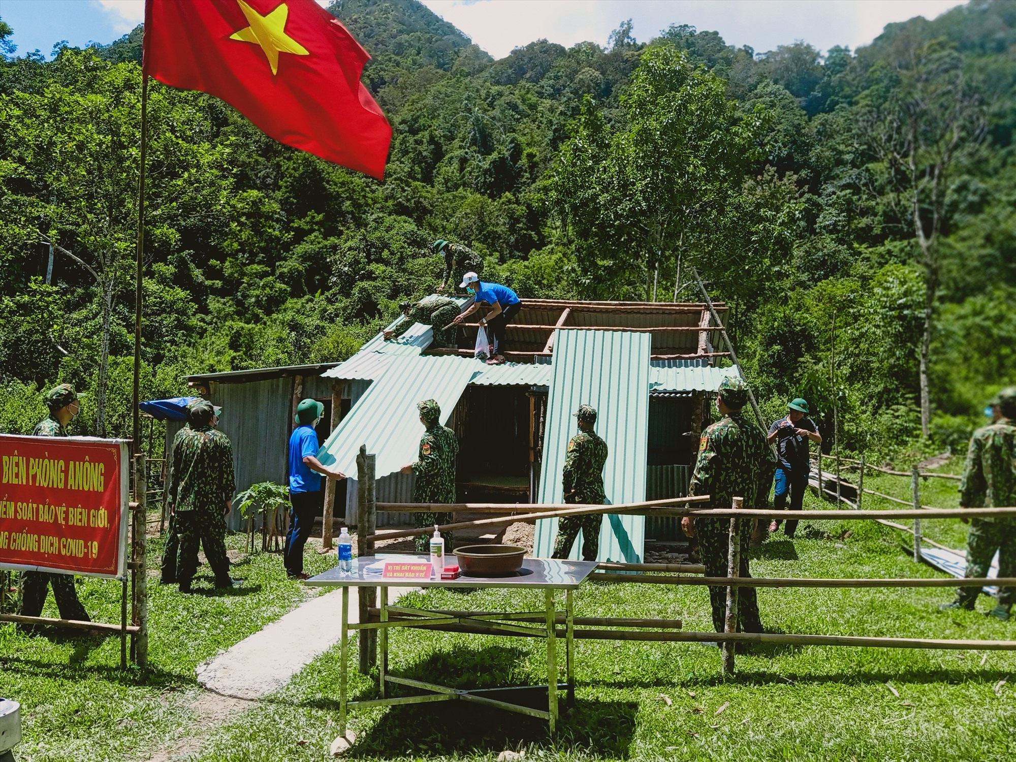 Đoàn viên thanh niên hỗ trợ cán bộ, chiến sĩ chốt 680 lợp mái tôn lán trại. Ảnh: HOÀNG LIÊN