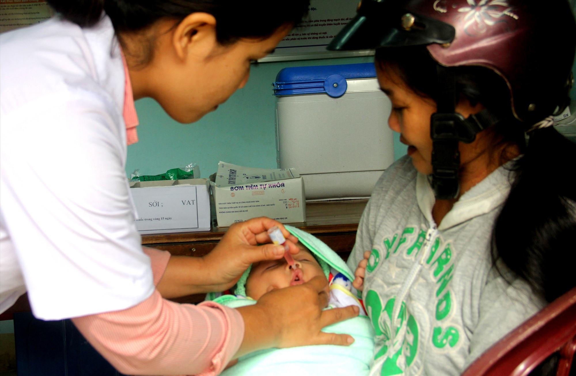 Y sĩ Trạm Y tế thị trấn Thạnh Mỹ (Nam Giang) nhỏ vắc xin cho trẻ sơ sinh. Ảnh: ĐĂNG NGUYÊN