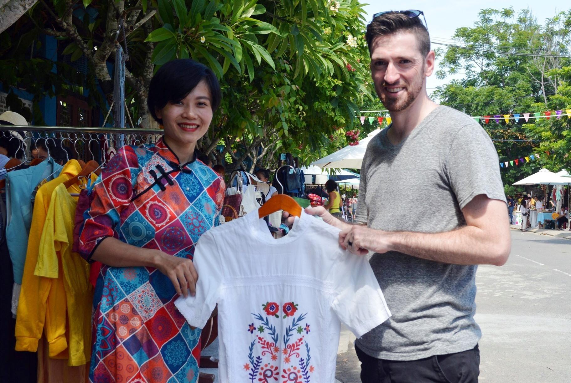 Một du khách thích thú khi chọn mua được chiếc áo ưa thích