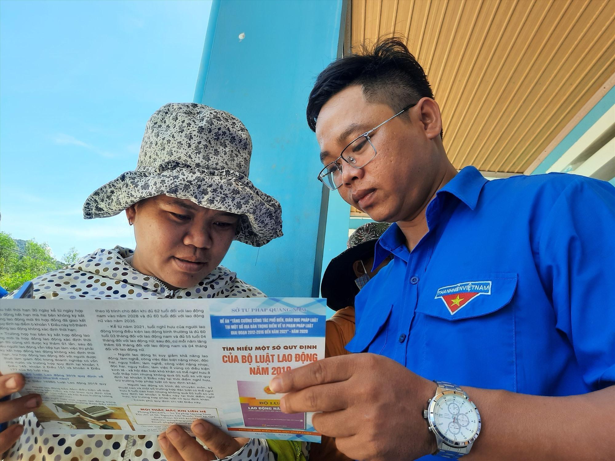 Cấp phát tờ rơi tuyên truyền các quy định mới của pháp luật Việt Nam năm 2020 cho người dân. Ảnh: HỒ QUÂN