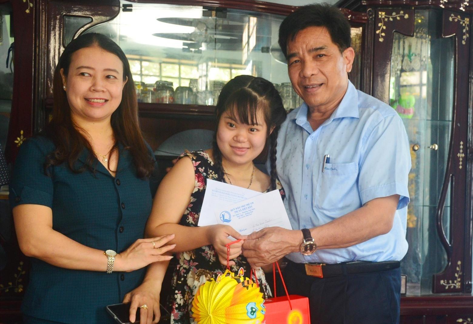 Trao quà cho một trẻ khuyết tật tại phường Điện Nam Đông. Ảnh: Q.T