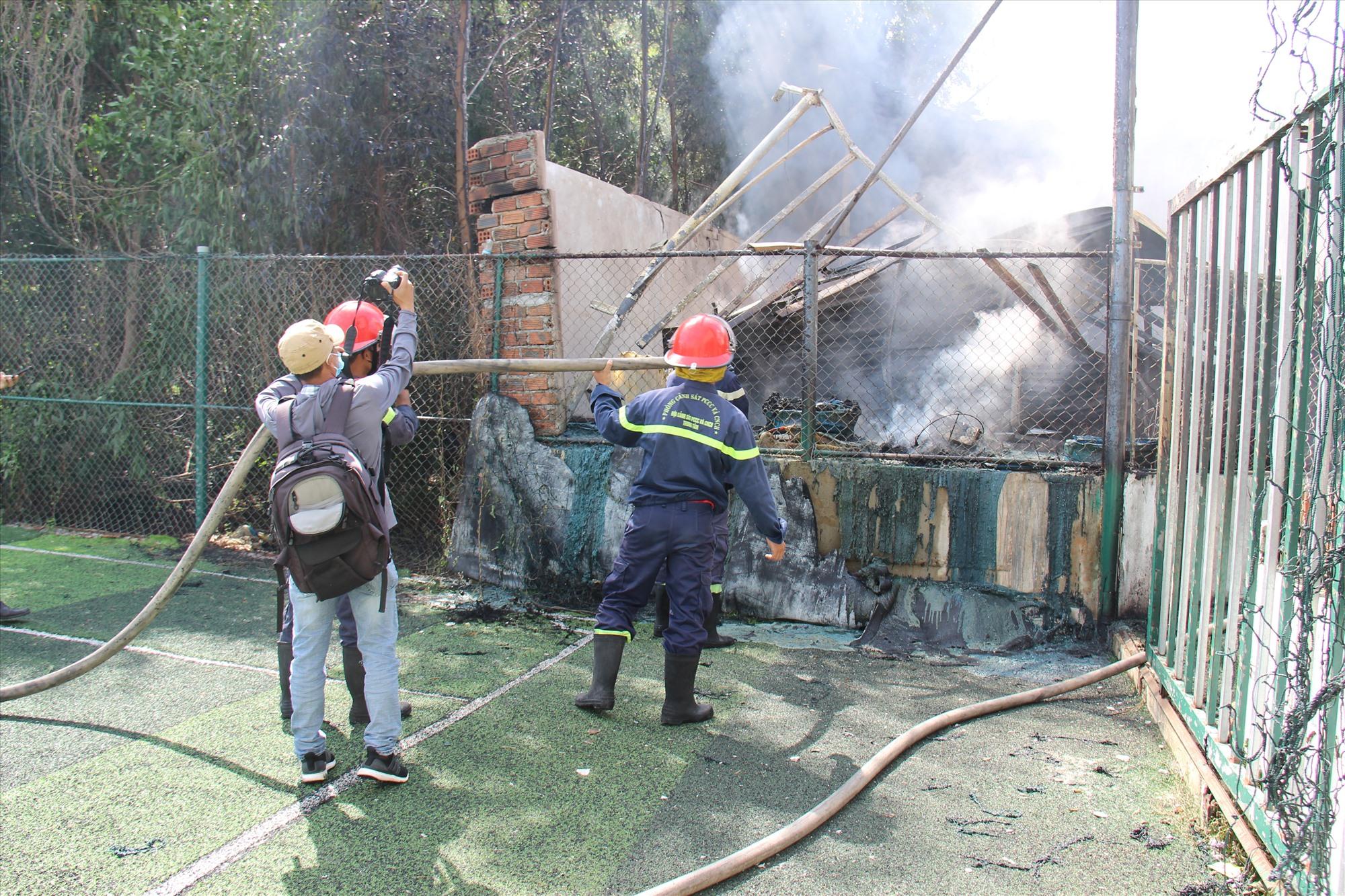 Cán bộ chiến sỹ tiến hành chữa cháy dập tắt ngọn lửa. Ảnh: HOÀI AN