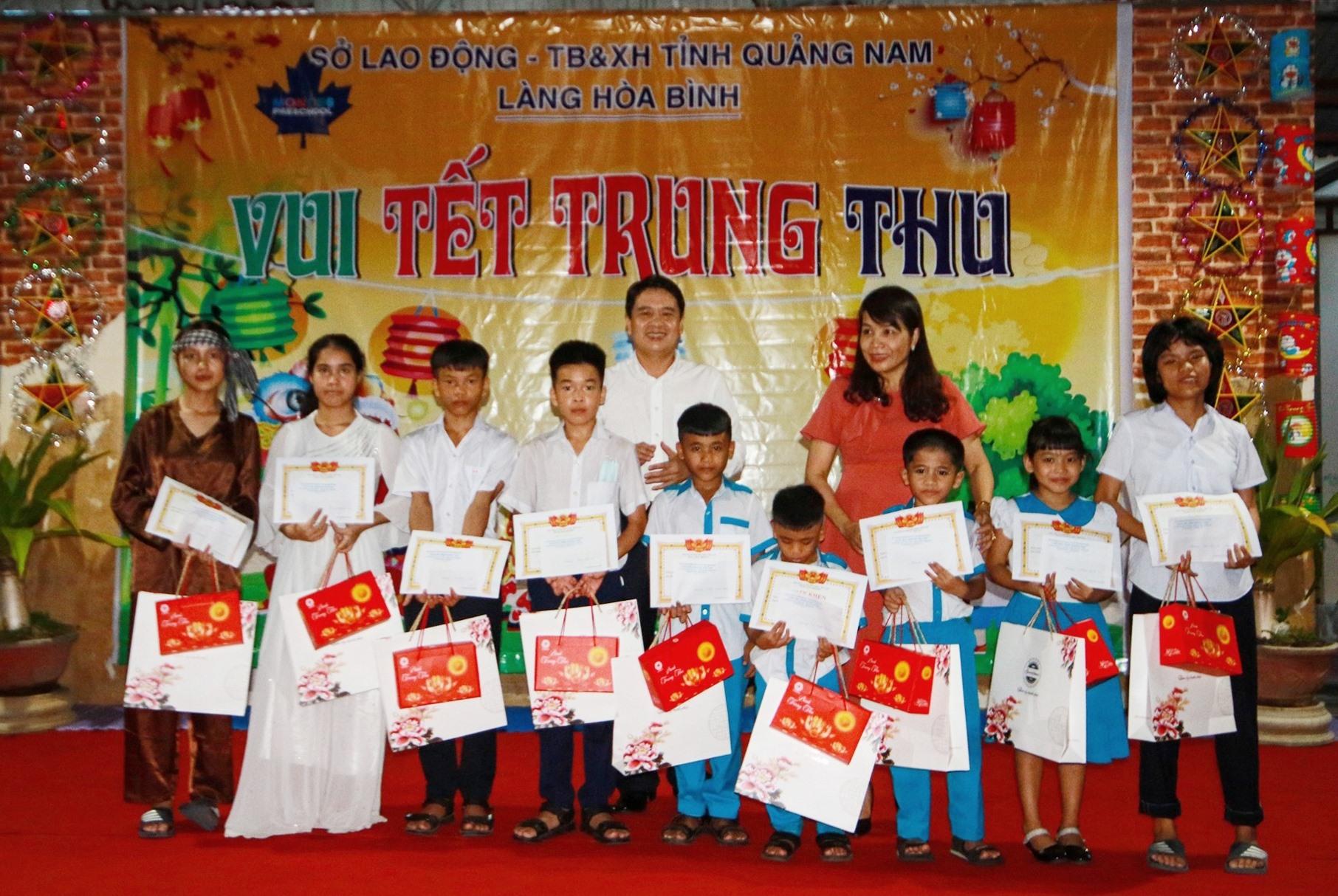 Phó Chủ tịch UBND tỉnh Trần Văn Tân và đại diện lãnh đạo Sở Lao động - Thương binh và Xã hội tỉnh tặng quà cho các em nhỏ có thành tích học tập xuất sắc. Ảnh: T.C