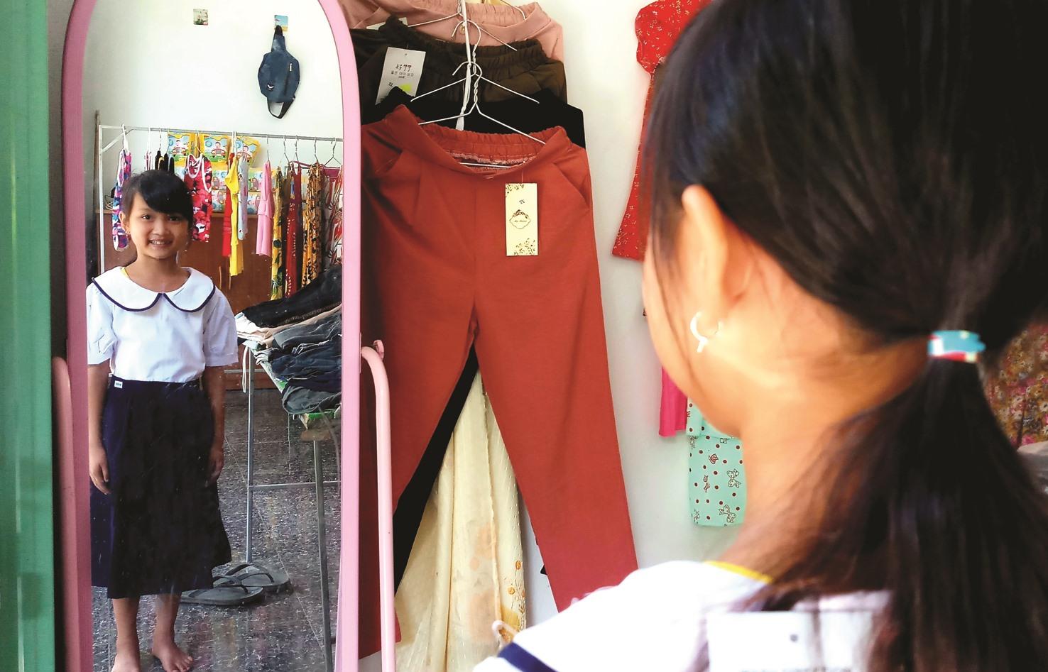 Một học sinh ở Trường Tiểu học Sông Kôn (huyện Đông Giang) ngắm nghía bộ trang phục mới.