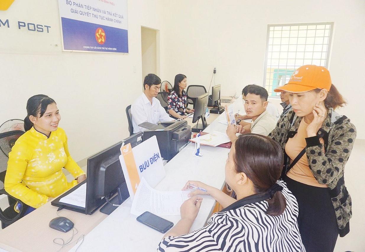 Người dân làm thủ tục hành chính tại Bưu điện xã Bình Triều, huyện Thăng Bình. Ảnh: B.Đ