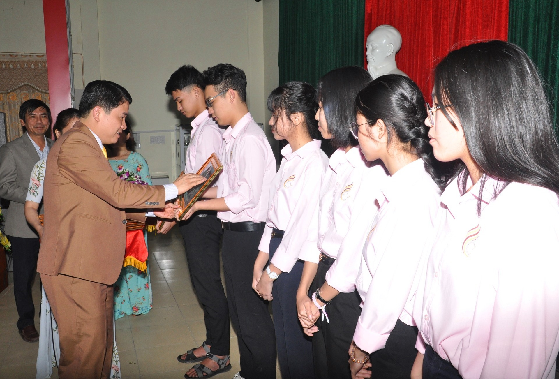 Phó Chủ tịch UBND tỉnh Trần Văn Tân tặng bằng khen cho cac em học sinh đoạt giải nhì. Ảnh: X.P