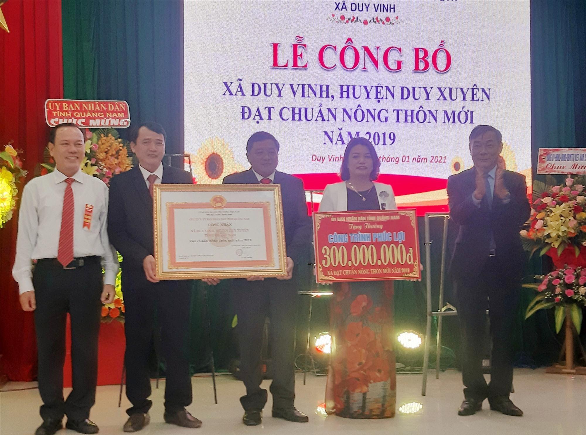 Lãnh đạo Văn phòng Điều phối NTM tỉnh và huyện Duy Xuyên trao bằng công nhận đạt chuẩn NTM năm 2019 cho xã Duy Vinh. Ảnh: T.S