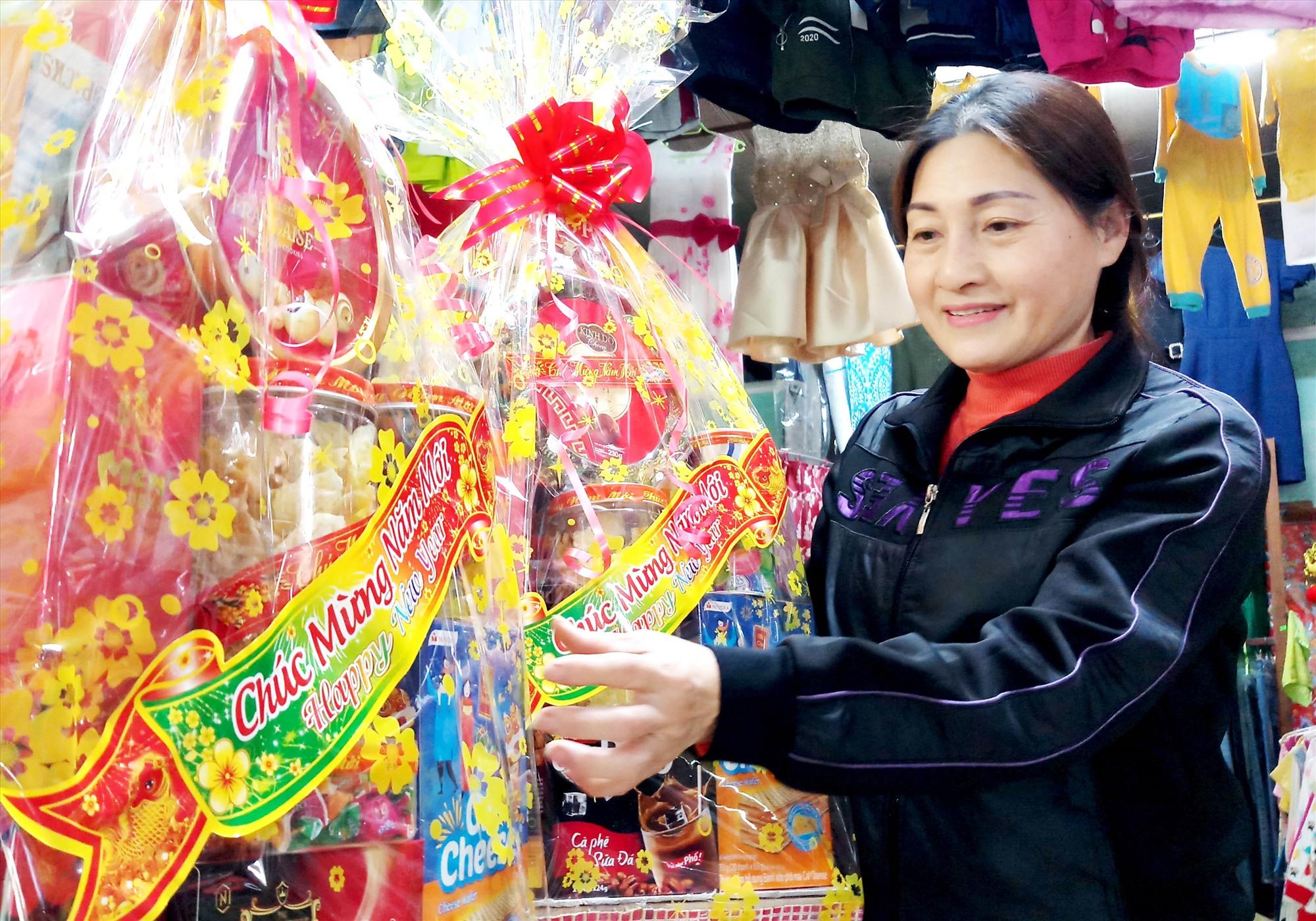 Vắng khách, thời gian gần đây, bà Nguyễn Thị Sâm - chủ tạp hóa Sâm Thông nhận gói những giỏ bánh kẹo được cơ quan, đơn vị đặt làm quà biếu. Ảnh: ĐĂNG NGUYÊN