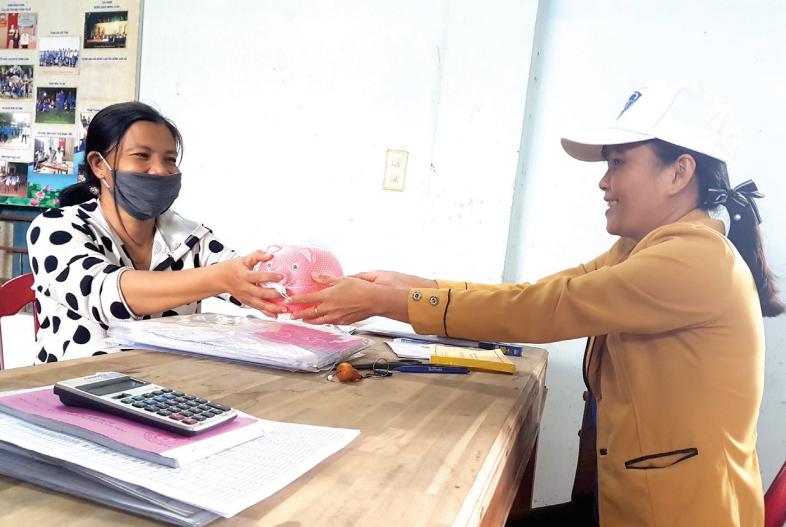 Đại lý thu ở cơ sở phát triển người tham gia chế độ BHXH tự nguyện bằng sáng kiến tặng con heo nhựa cho người dân. Ảnh: D.L