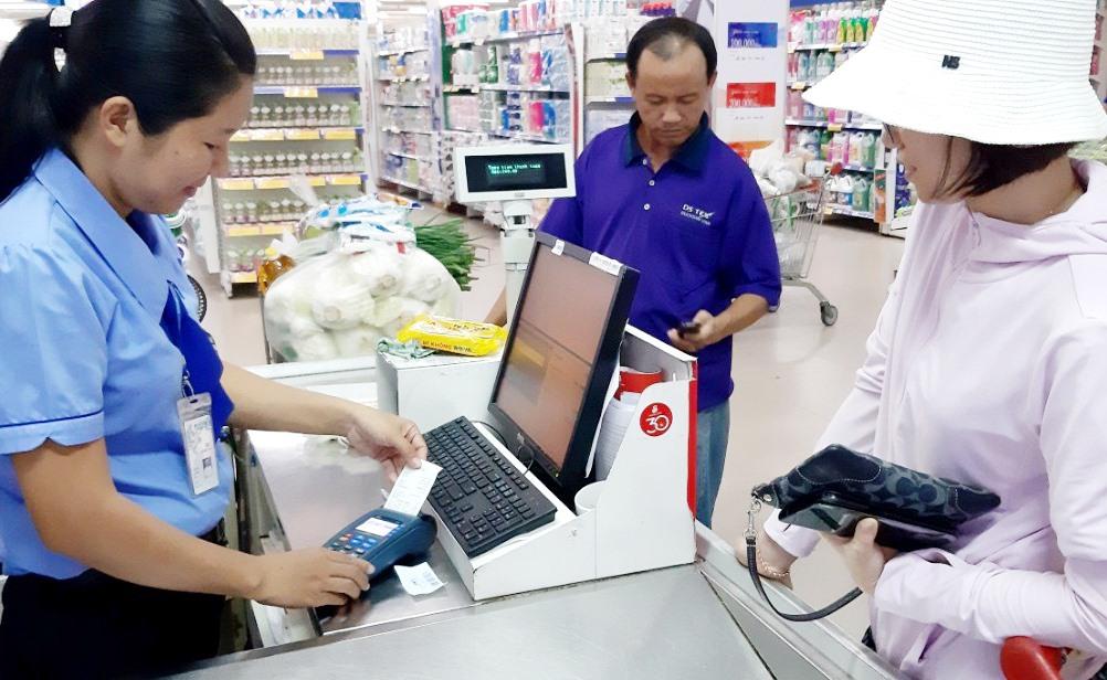 Doanh nghiệp dùng máy POS để tiện lợi cho thanh toán qua thẻ ngân hàng của người dân. Ảnh: VIỆT NGUYỄN