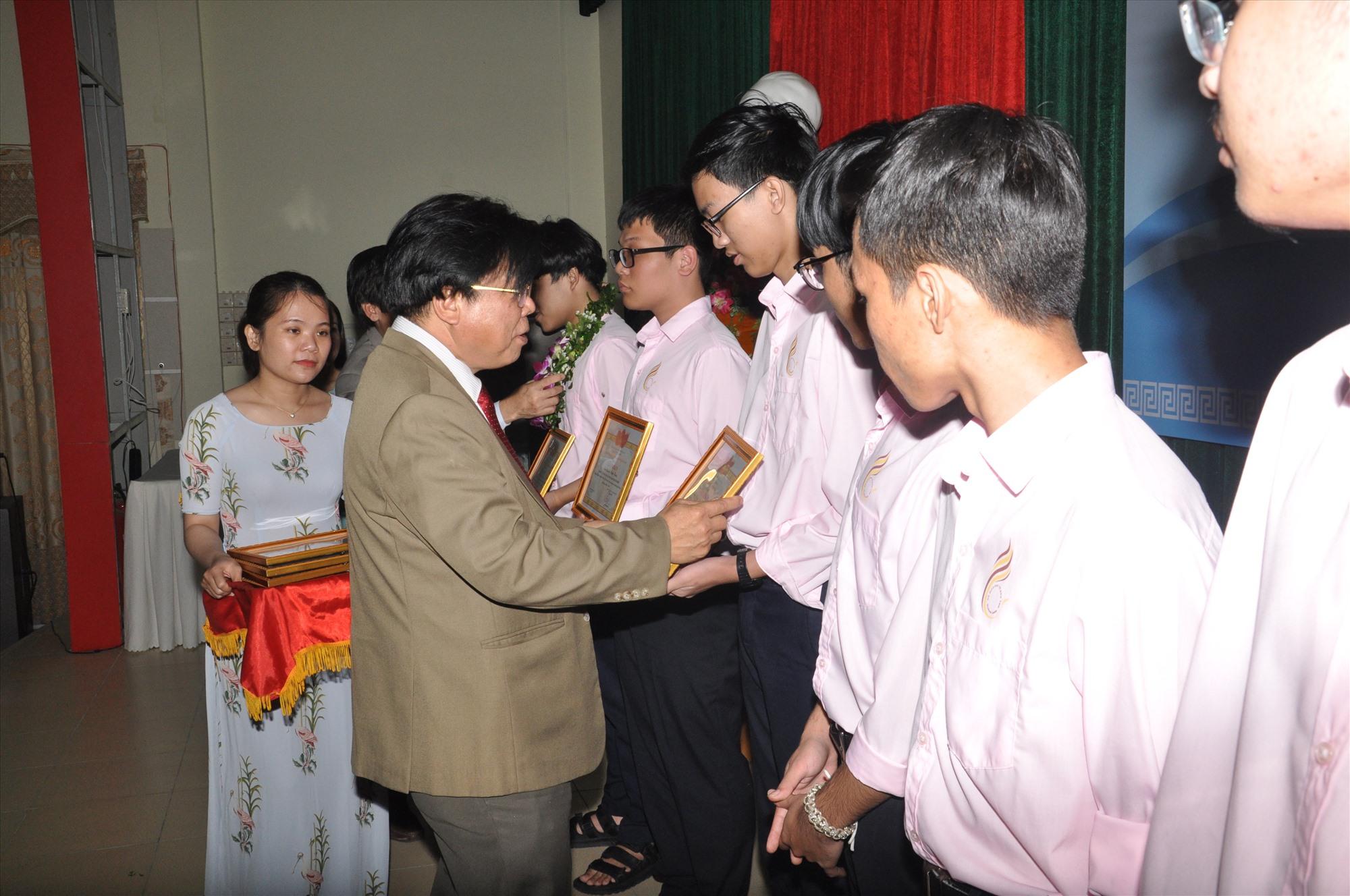 Ông Hà Thanh Quốc khen thưởng học sinh đoạt giải học sinh giỏi quốc gia năm học 2020 - 2021. Ảnh: X.P