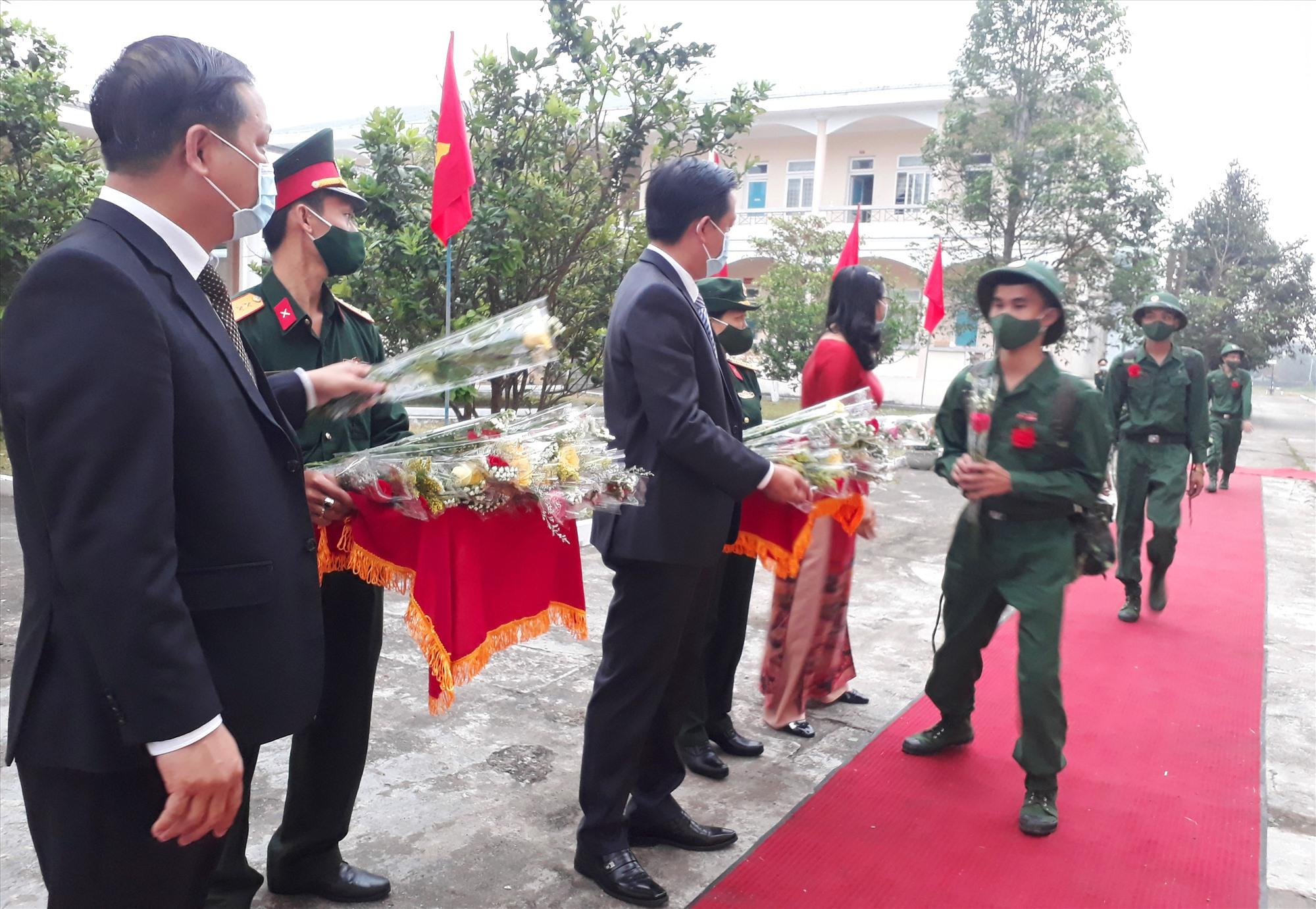 Lãnh đạo huyện Quế Sơn tặng hoa chúc mừng các tân binh. Ảnh: T.L