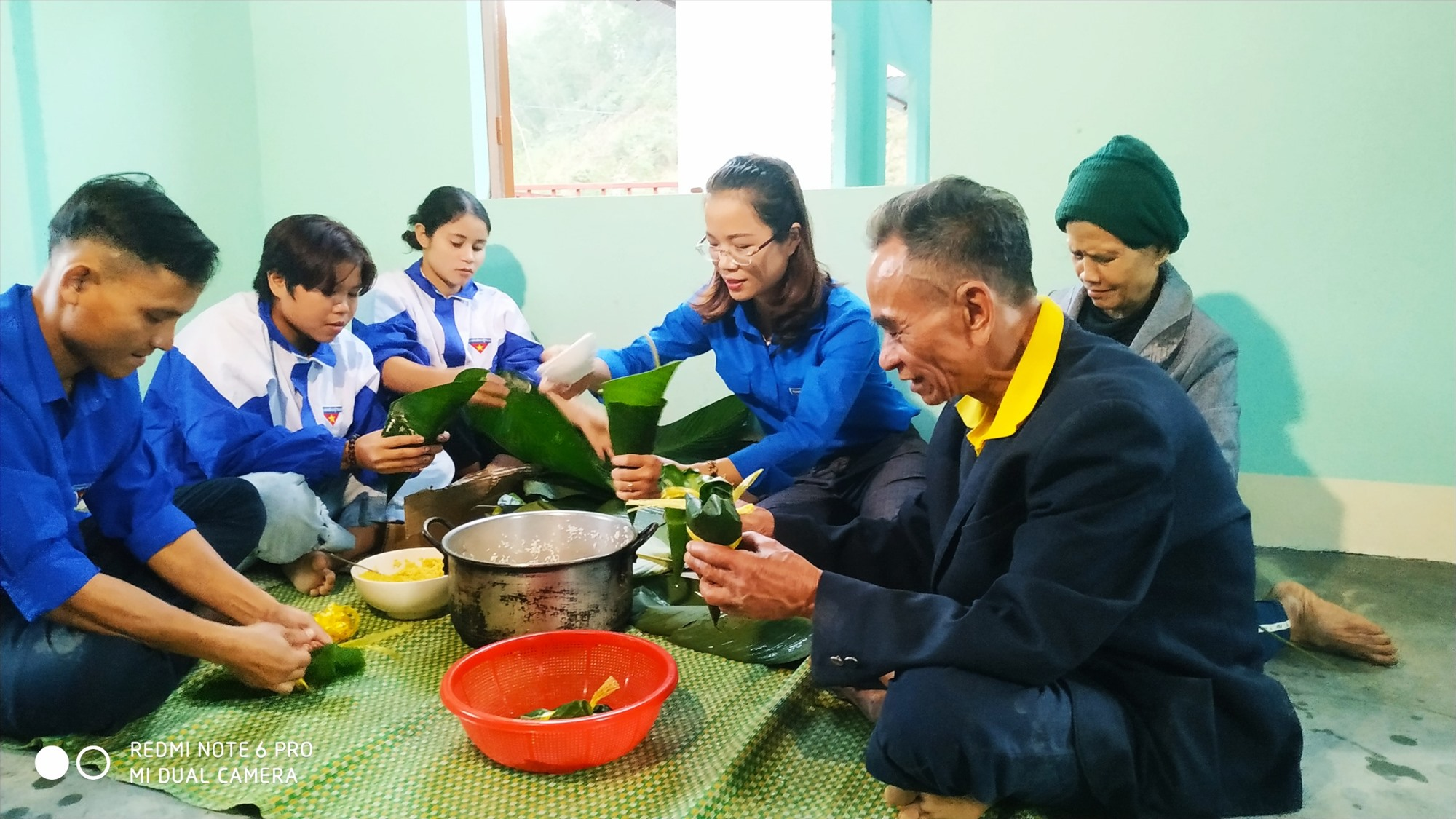 Đoàn viên thanh niên cùng gia đình ông Hồ Văn Đề gói bánh, nấu bánh, chuẩn bị cho bữa cơm tất niên, dọn về nhà mới. Ảnh: M.HẠNH