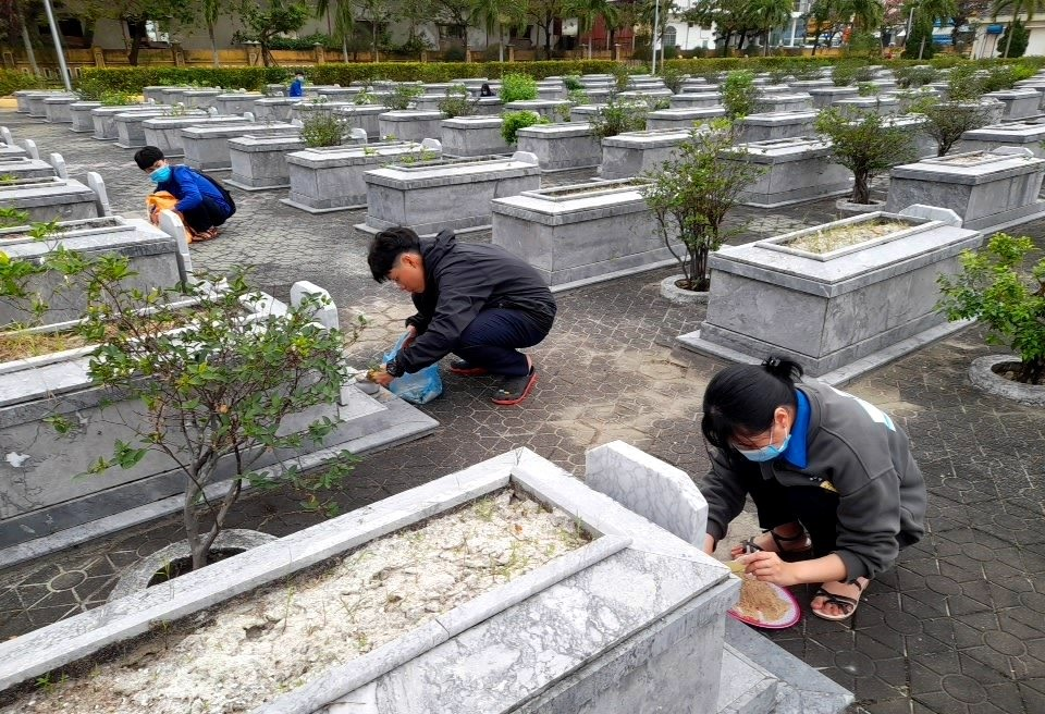Học sinh Trường THPT Lê Quý Đôn tổ chức quét dọn và thay cát hơn 500 lư hương tại Nghĩa trang liệt sĩ TP.Tam Kỳ. Ảnh: Đ.N