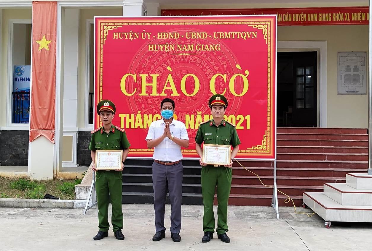 Chủ tịch UBND huyện Nam Giang - ông A Viết Sơn trao giấy khen cho đại diện Công an huyện trong buổi chào cờ sáng nay 1.3. Ảnh: A.L.T