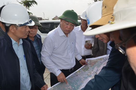 Chairman Le Tri Thanh (middle) and the planning map of East Quang Nam.