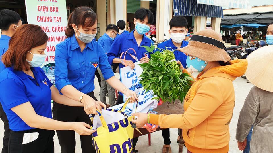 Phát miễn phí túi xách thân thiện với môi trường cho người dân đi chợ tại chợ Phong Thử (Điện Thọ). Ảnh: Thị đoàn Điện Bàn.
