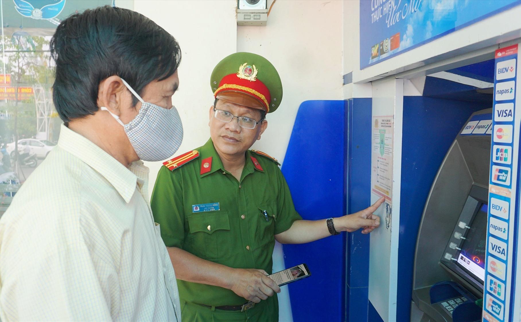 Cán bộ Công an tuyên truyền cho người dân biện pháp phòng chống tội phạm lừa đảo qua mạng xã hội tại trụ ATM.