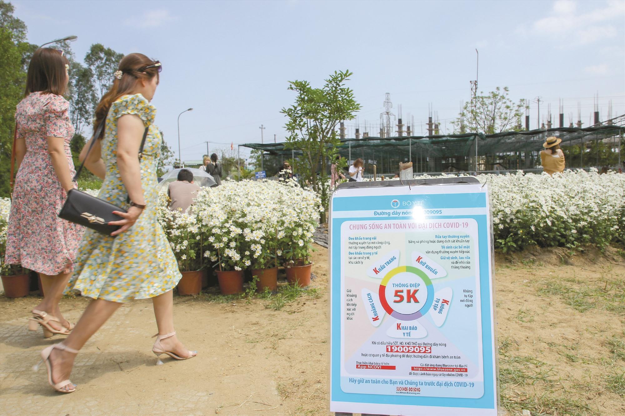 """Tại vườn hoa đặt biển tuyên truyền thông điệp """"5K"""" của Bộ Y tế về phòng chống dịch Covid-19. Khách khi vào cổng, được đo thân nhiệt, sát khuẩn tay."""
