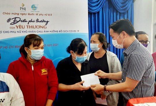 Đại diện PNJ trao tiền hỗ trợ cho phụ nữ tại TP. Hồ Chí Minh