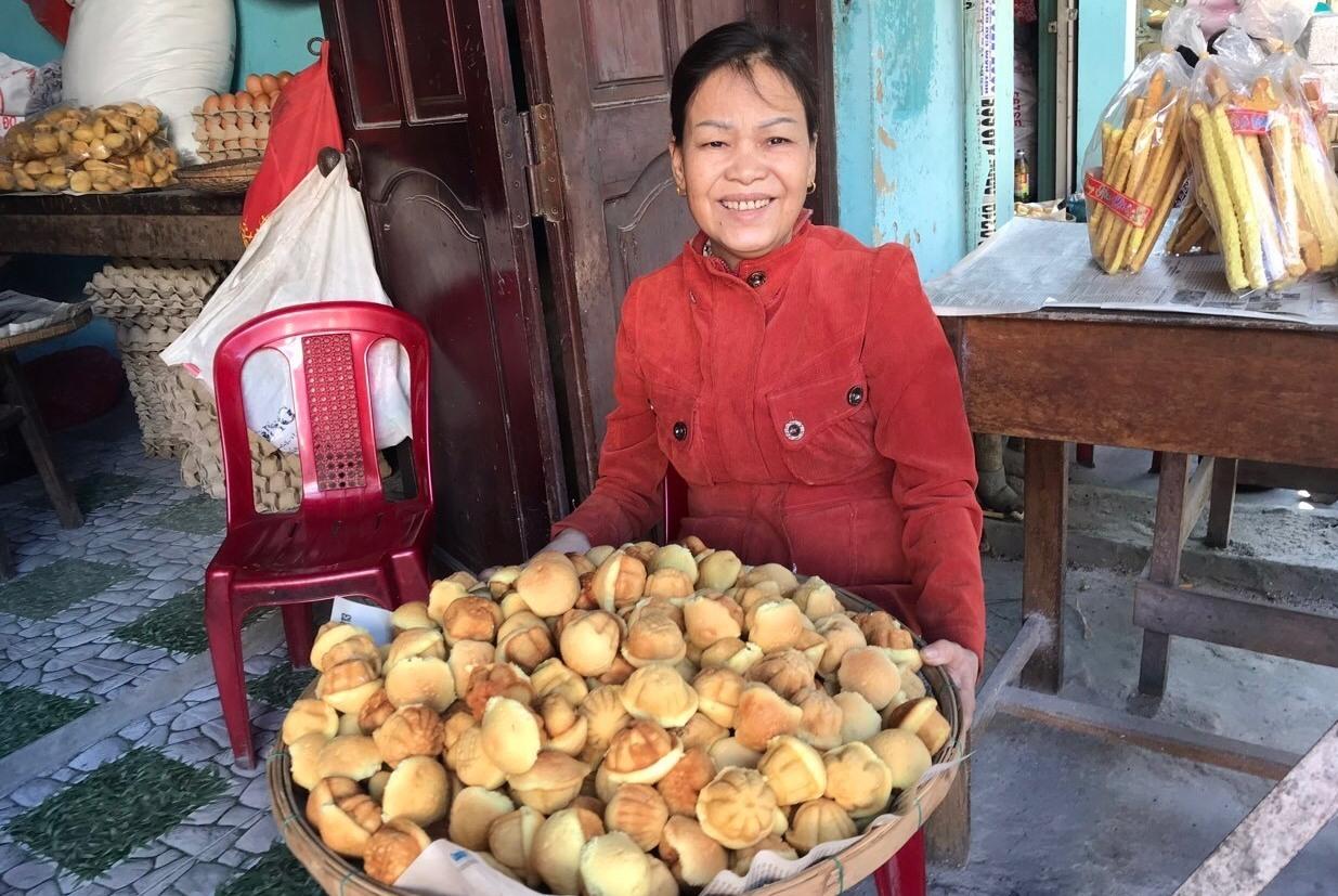 Bà Huỳnh Thị Xí bên nia bánh thuẫn mới ra lò. Ảnh: N.Trang