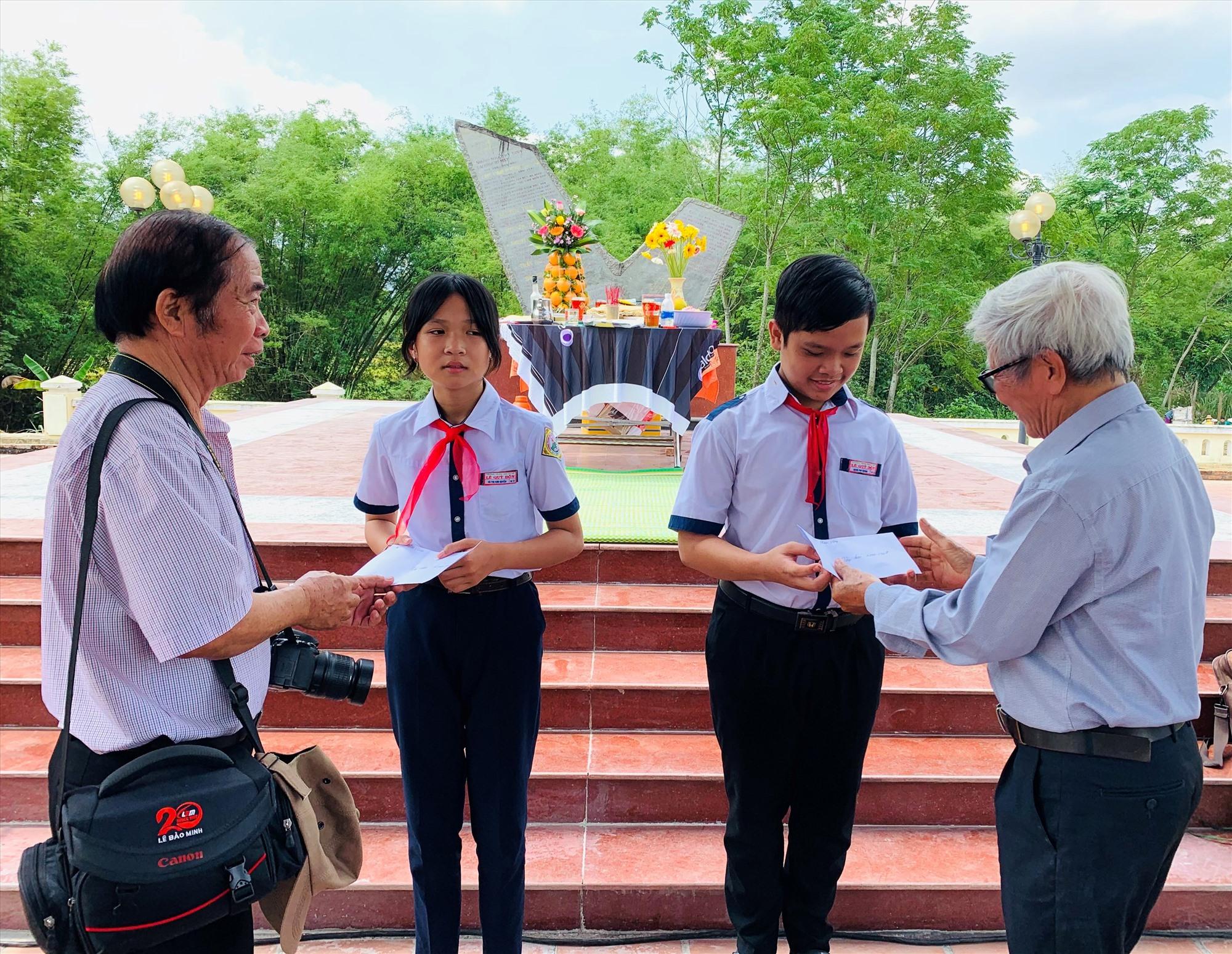 Các nhà văn, nhà báo ở Quảng Nam và Đà Nẵng tặng học bổng cho học sinh khó khăn của xã Duy Tân. Ảnh: T.S