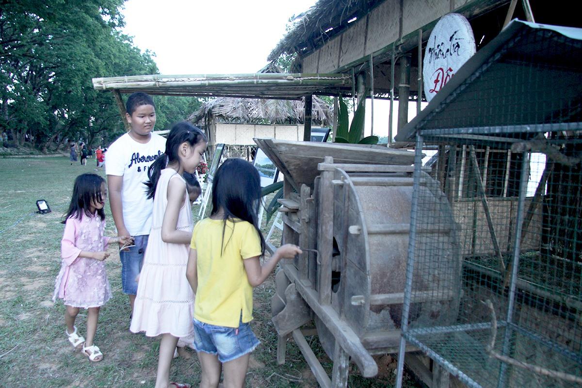Các em nhỏ thích thú với máy xay lúa.