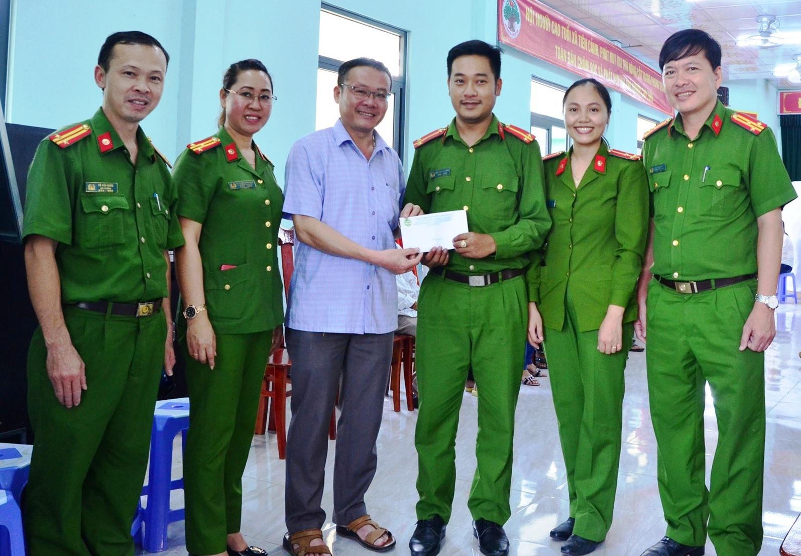 Chủ tịch UBND huyện Tiên Phước Trầm Quế Hương và lãnh đạo công an huyện tặng quà cho cán bộ, chiến sĩ làm CCCD tại xã Tiên Cảnh.
