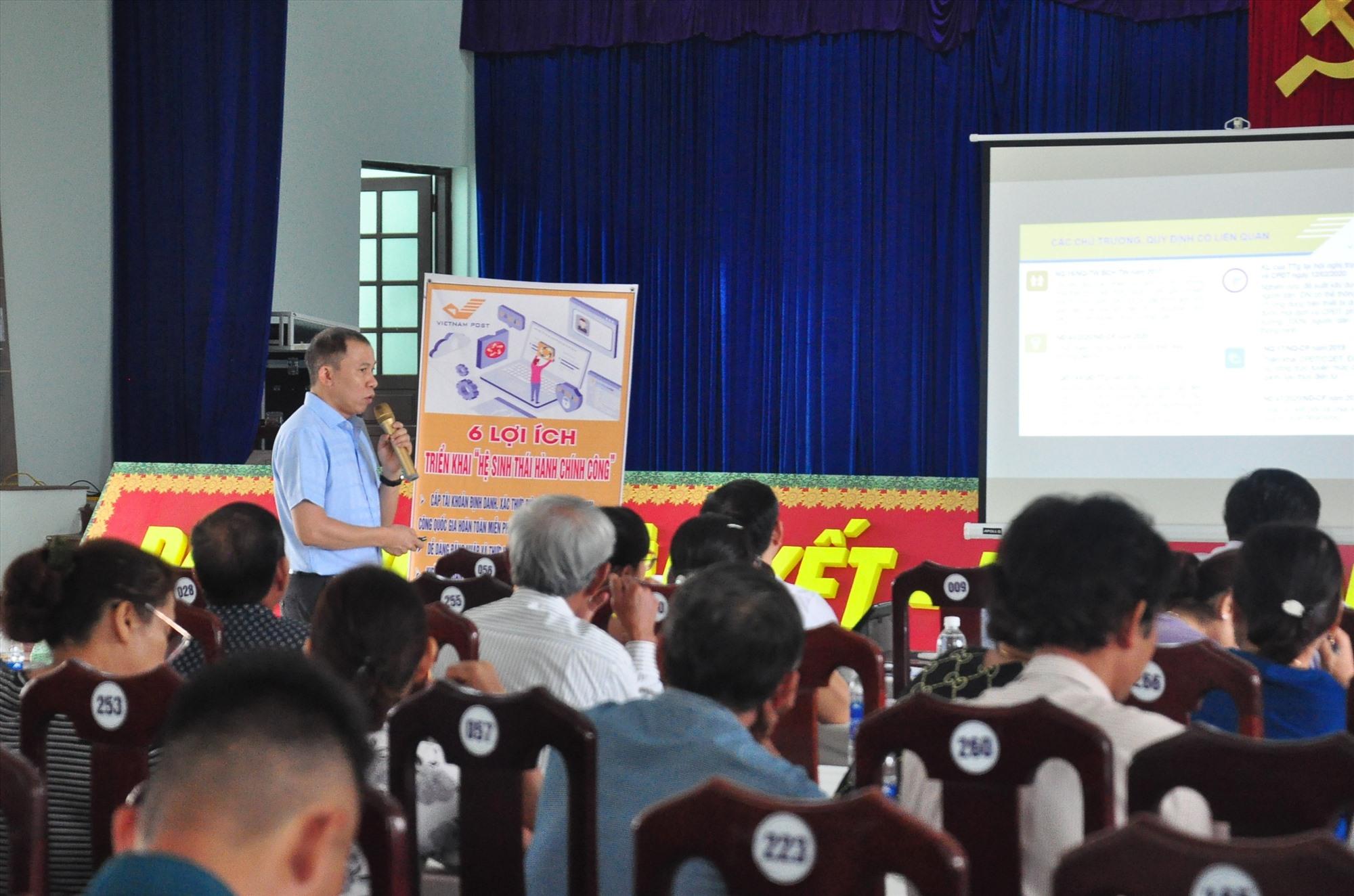 """Cán bộ, người dân thị trấn Nam Phước được nhân viên bưu điện giới thiệu về """"Hệ sinh thái hành chính công"""". Ảnh: V.A"""