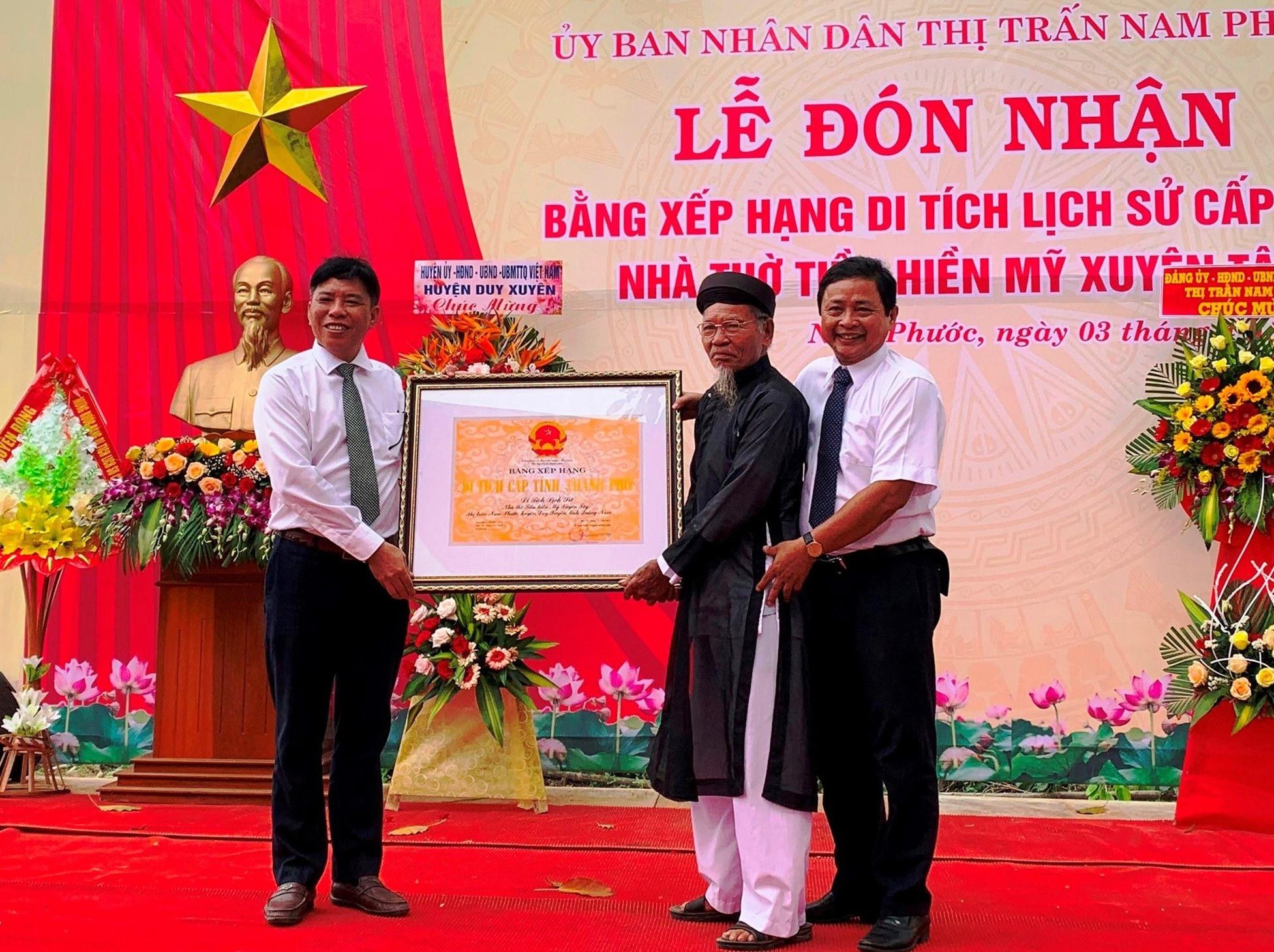Đại diện lãnh đạo UBND huyện Duy Xuyên trao bằng công nhận di tích lịch sử cấp tỉnh - nhà thờ tiền hiền Mỹ Xuyên Tây cho ban đại diện làng. Ảnh: T.L
