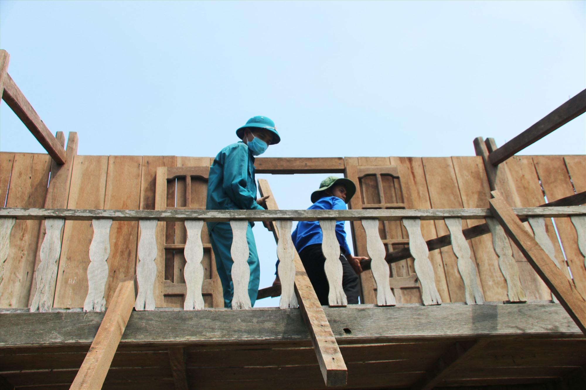 Dân quân và đoàn viên thanh niên xã Đắc Tôi, huyện Nam Giang hỗ trợ người dân lợp lại nhà cửa. Ảnh: BÌNH AN