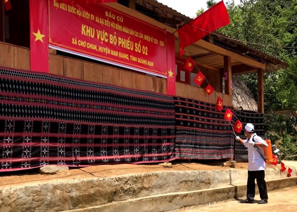 Phun thuốc khử khuẩn tại điểm bầu cử sớm ở Nam Giang. Ảnh: A LĂNG NGƯỚC