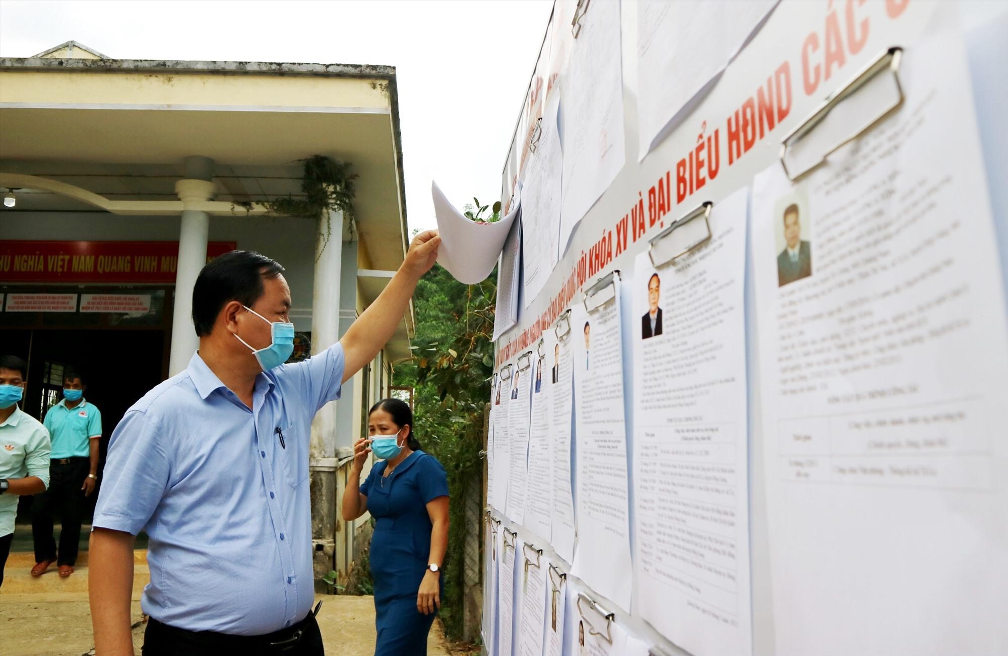 Đồng chí Nguyễn Hồng Quang kiểm tra danh sách cử tri, danh sách người ứng cử được niêm yết tại một đơn vị bầu cử huyện Đông Giang. Ảnh: A.N