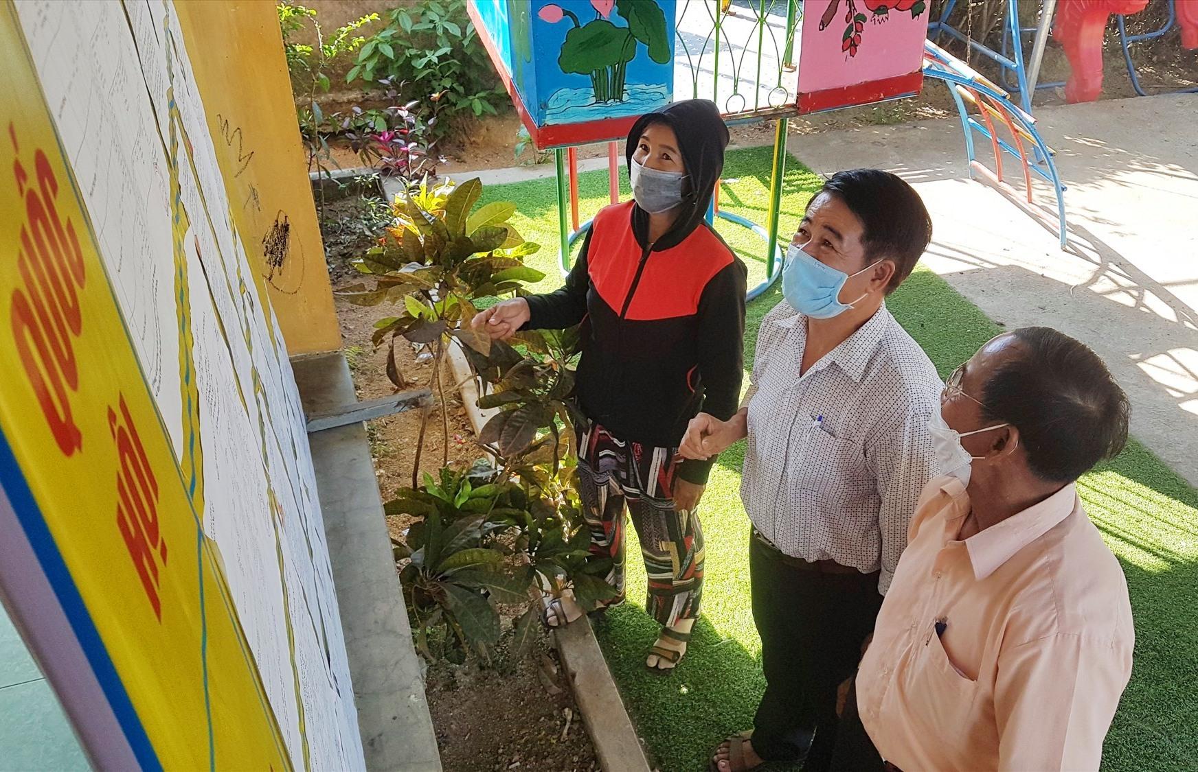 Cử tri đến tìm hiểu thông tin ứng cử viên tại một điểm bỏ phiếu bầu cử ở Tiên Phước. Ảnh: D.L