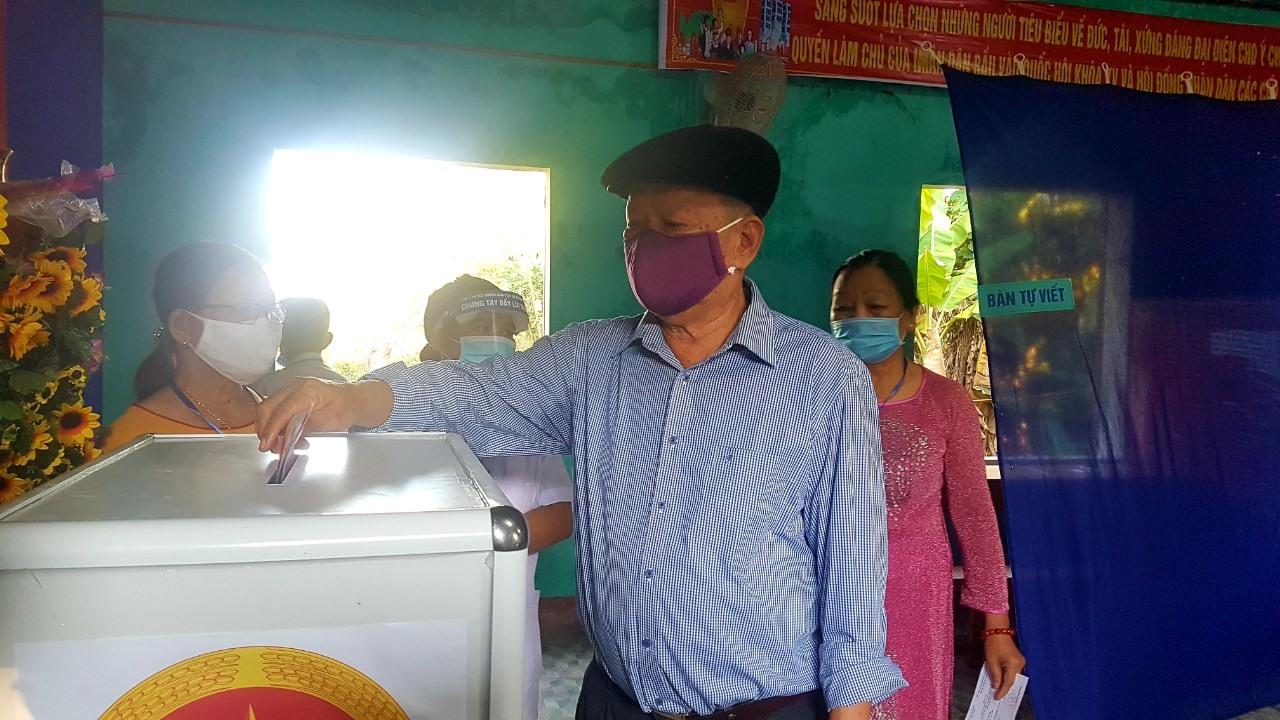 Cử tri Nguyễn Xuân Quang bỏ lá phiếu bầu cử đầu tiên vào thùng phiếu.