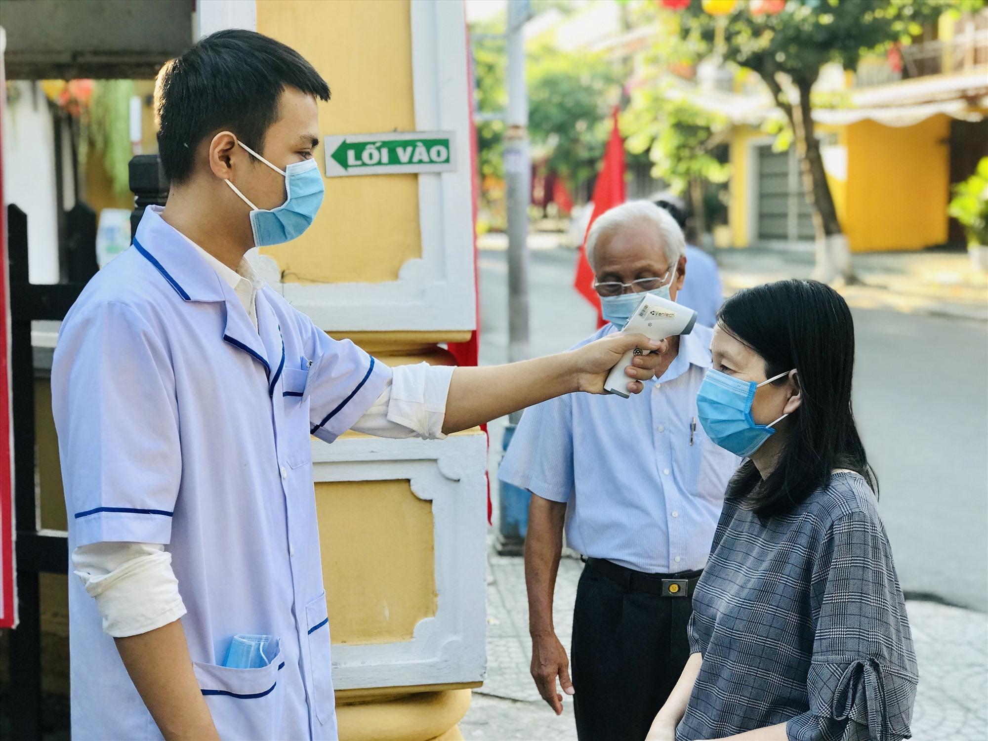 Lực lượng y tế đo thân nhiệt cho cử tri tại phường Cẩm Phô.