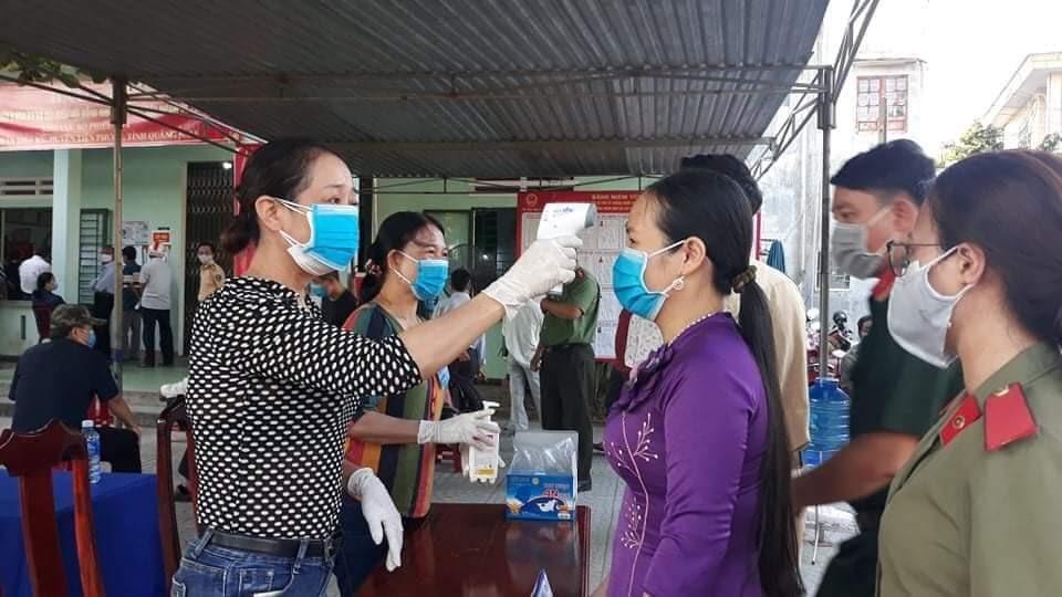Cử tri Tiên Phước được đo thân nhiệt trước khi vào khu vực bỏ phiếu.